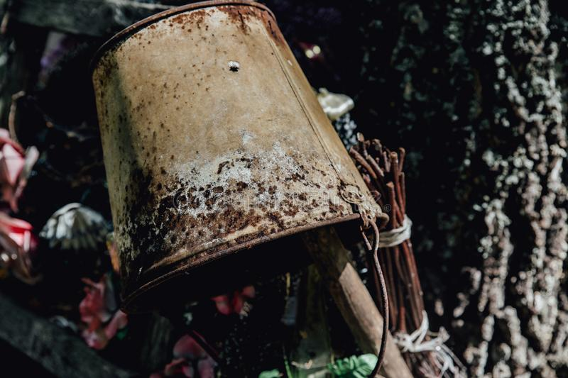 The letters on a rusting bucket with twisted wire handle near the early 1900s homestead of Faraway Ranch. In the summer forest Bucket Outdoors, An old pail stock photo