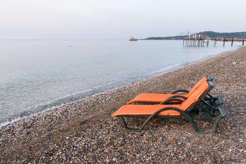 Letti di plastica del sole con i capi arancio sulla spiaggia del mare ad alba Concetto di vacanze estive fotografia stock libera da diritti