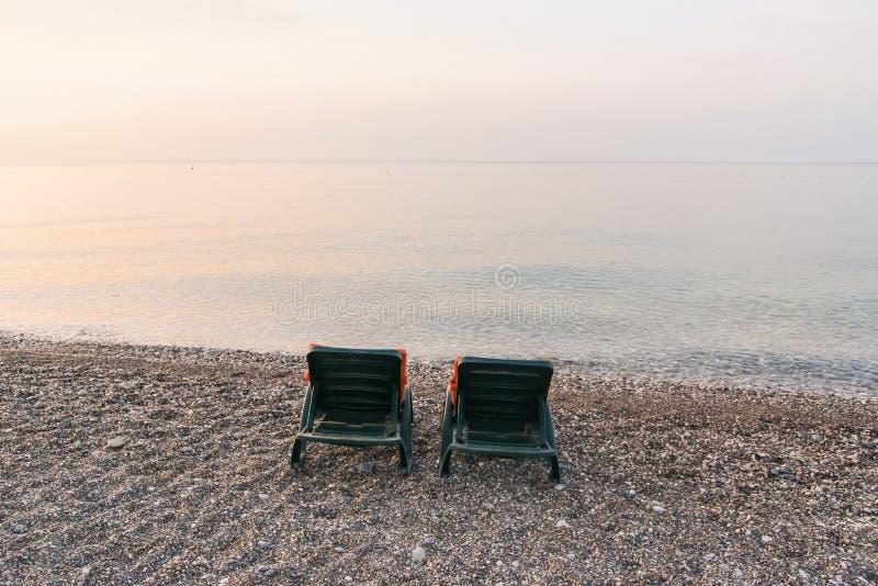 Letti di plastica del sole con i capi arancio sulla spiaggia del mare ad alba Concetto di vacanze estive immagini stock