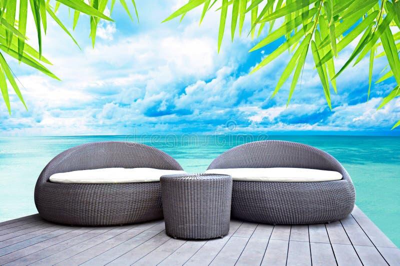 Letti di sofà di vimini di rilassamento vicino il mare fotografie stock libere da diritti