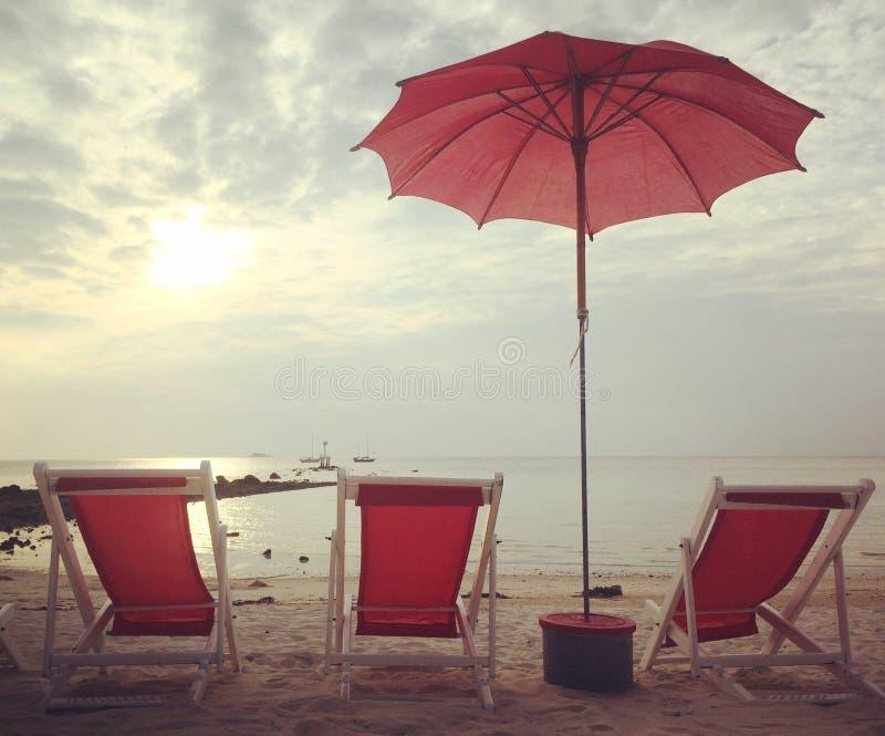 Letti ed ombrello rossi della spiaggia sul tramonto bianco della spiaggia immagine stock libera da diritti