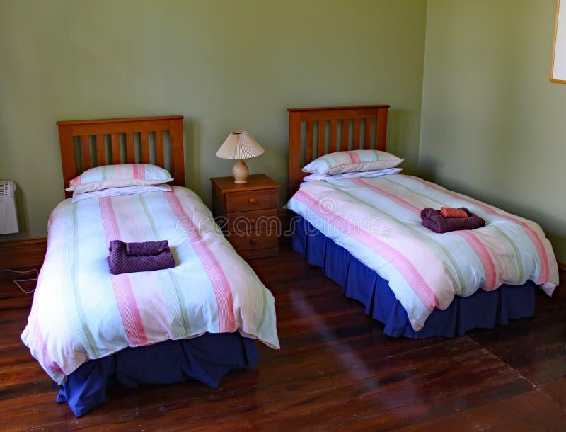 Letti gemellati in una proprietà soggetta a locazione originale in Distretto di Masterton in Nuova Zelanda immagine stock