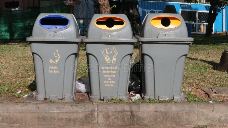 Lettiera fra i bidoni della spazzatura ad un parco pubblico fotografia stock