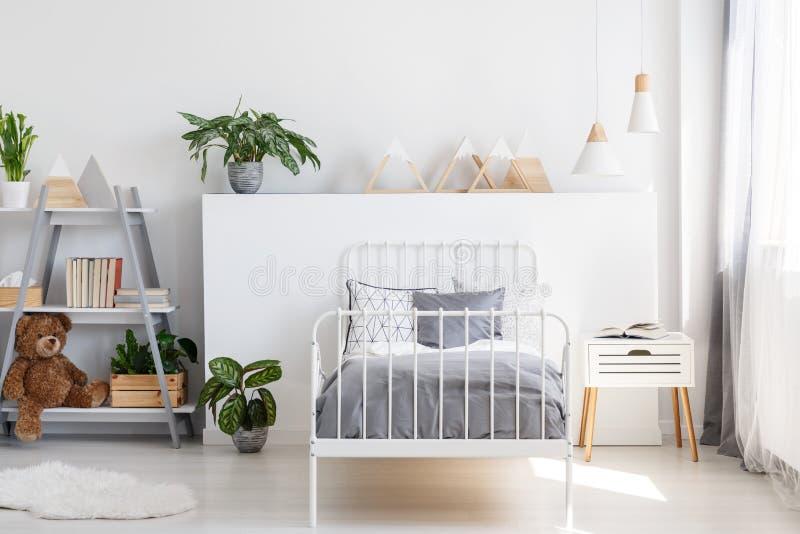 Lettiera grigia su un letto singolo con la struttura del metallo e un comodino scandinavo di stile in un bello, interno luminoso  fotografia stock