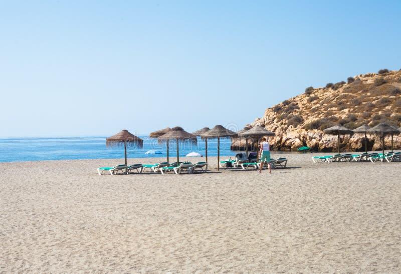Lettini ed ombrelli della paglia sulla spiaggia immagini stock libere da diritti