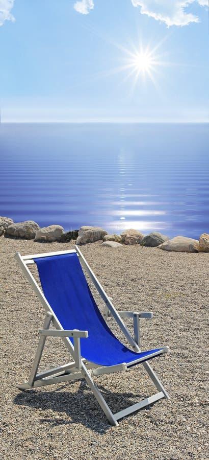 Lettino alla spiaggia pietrosa, all'acqua ondulata blu ed al sole luminoso immagine stock