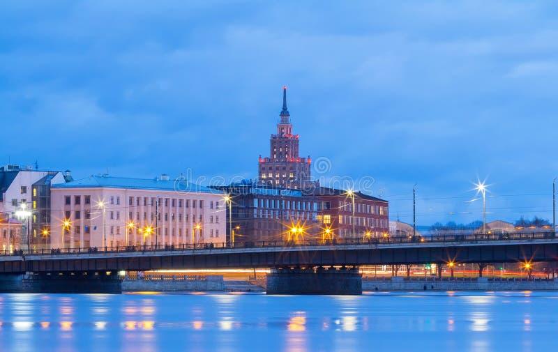 Lettisk akademi av vetenskaper, stenbron och floddaugavaen på natten, Riga, Lettland fotografering för bildbyråer