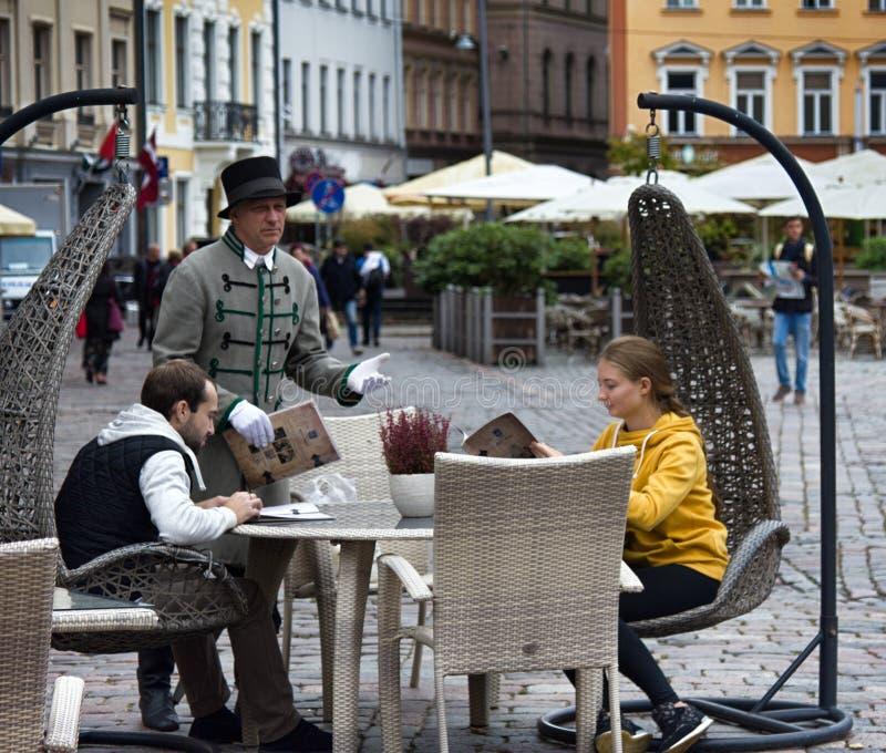 Lettiskt besökaregatakafé och uppassare i form av institutioner royaltyfri fotografi