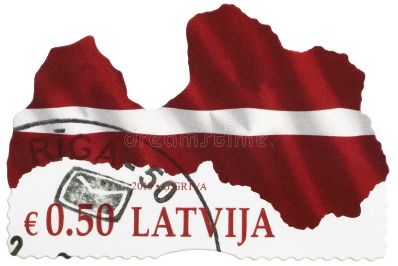 LETTLAND - 2018: Eine zeitgenössische Briefmarke gedruckt in LETTLAND, stilisierte rote weiße Flagge des Republik Lettlands, Euro lizenzfreies stockfoto
