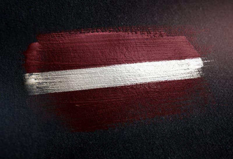Lettland flagga som göras av metallisk borstemålarfärg på Grungemörkerväggen arkivbild