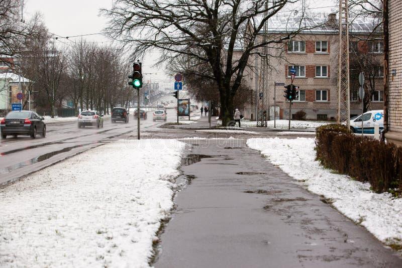 Lettland Riga - December 1 2017: Blöta insnöat staden, trafiken och folket på de hala gatorna arkivfoton