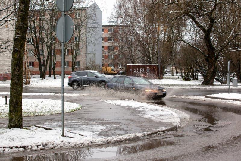 Lettland Riga - December 1 2017: Blöta insnöat staden, trafiken och folket på de hala gatorna royaltyfria bilder