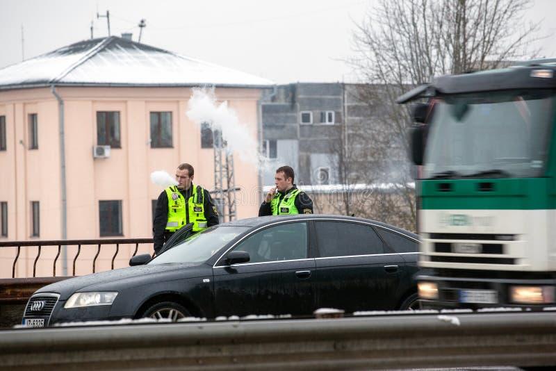 Lettland, Riga - 1. Dezember 2017: Städtische Polizei von Riga, Lettland am Unfallort durch das Auto Rauchende elektronische ciga stockbild