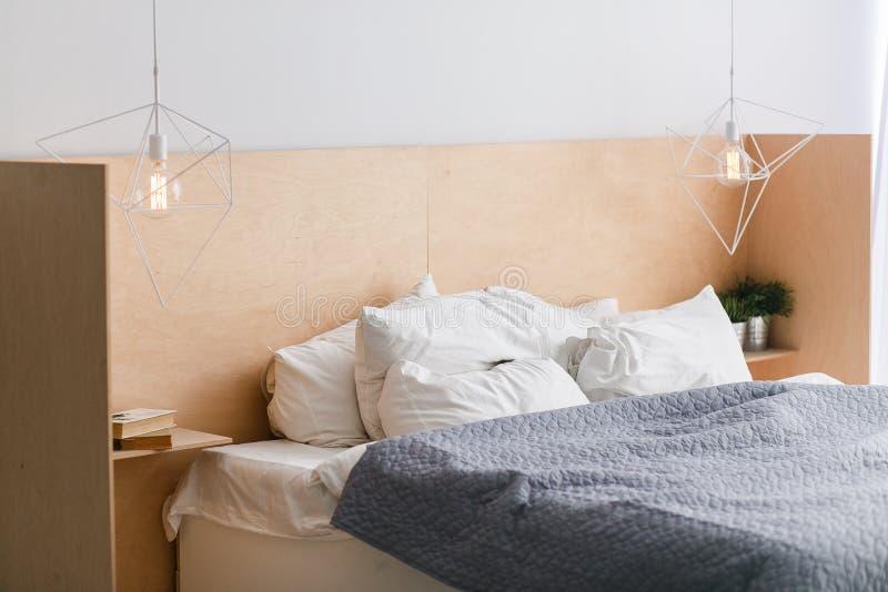 Letto in bianco e nero con bedhead di legno in sottotetto interno, luci geometriche immagine stock