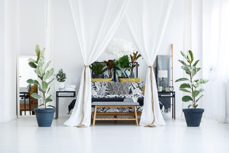 Letto circondato dalle piante fotografia stock