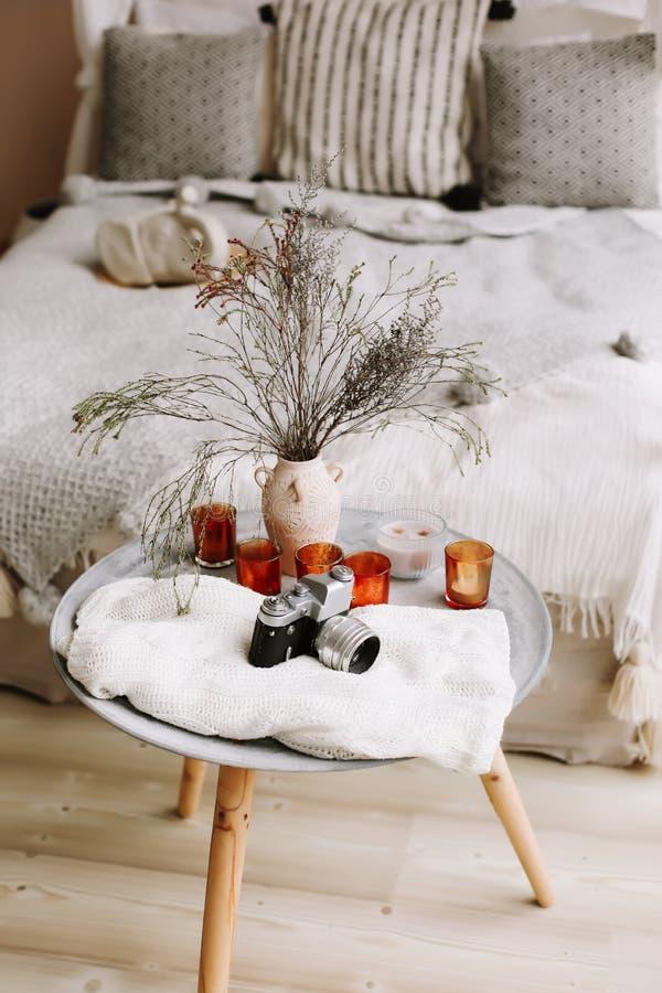 Letto con i cuscini, la coperta e un comodino con la retro macchina fotografica e candele Interno esotico della camera da letto,  fotografia stock
