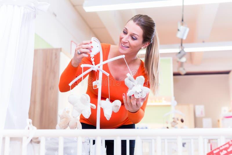 Letto di bambino d'acquisto della donna incinta in deposito immagine stock libera da diritti