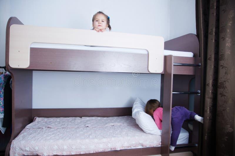Letto di cuccetta nella stanza di bambino bambina due che gioca sul letto ombra del cioccolato nell'interno con le pareti bianche immagini stock libere da diritti