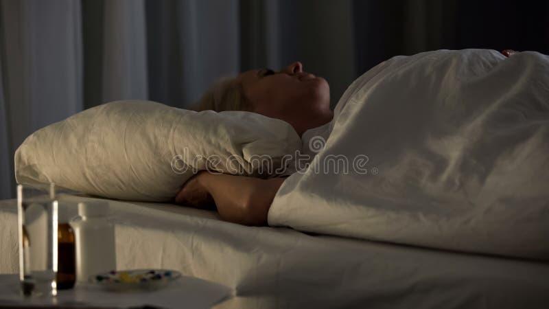 Letto di ospedale seriamente malato di sonno della donna con la tavola delle pillole dell'antidolorifico, malattia fotografia stock libera da diritti