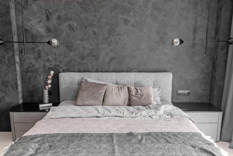 Letto grigio in camera da letto monocromatica con i cuscini e le lampade del sottotetto sulla parete immagine stock libera da diritti