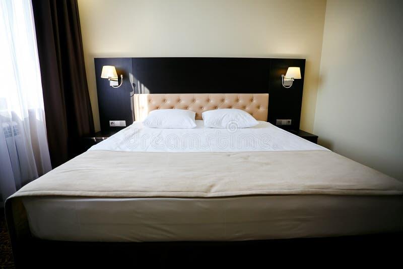 Letto matrimoniale nella camera di albergo ordinaria Luce del giorno come fondo Governo della casa, servizio in camera, pulente immagini stock