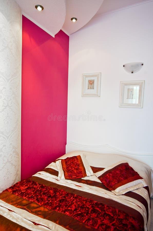 Letto nella sala con la parete rossa di accento fotografia stock