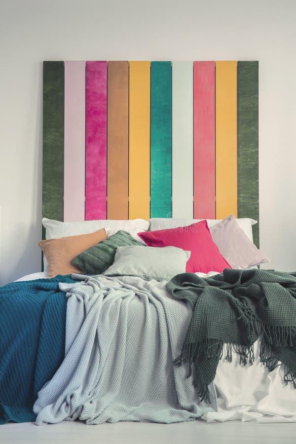 Letto variopinto nell'interno bianco della camera da letto Foto reale dei cuscini gialli, grigi, verdi e rosa sugli strati bianch fotografia stock libera da diritti