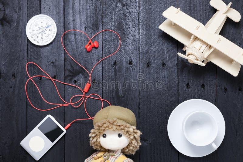 Lettore con il trasduttore auricolare rosso, tazza di caffè macchiato, aeroplano di legno immagini stock