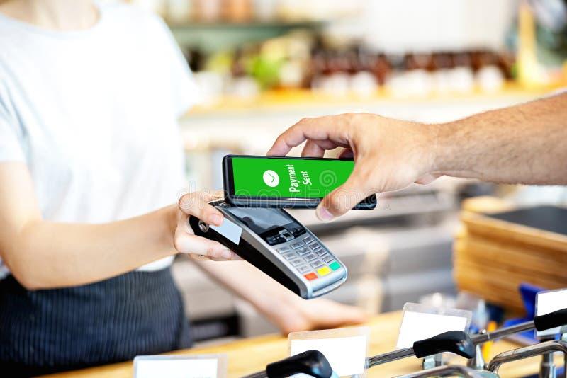 Lettore di schede della tenuta della cameriera di bar per l'uomo che paga dallo smartphone al deposito, cliente che per mezzo del fotografia stock