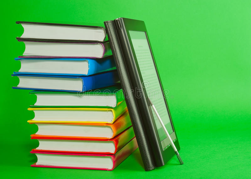 Lettore elettronico del libro con la pila di libri stampati immagini stock
