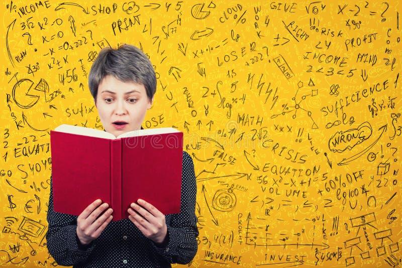 Lettore stordito della donna che sembra stupito in un libro Calcoli di matematica, formula di economia ed equazioni difficili ris fotografie stock libere da diritti