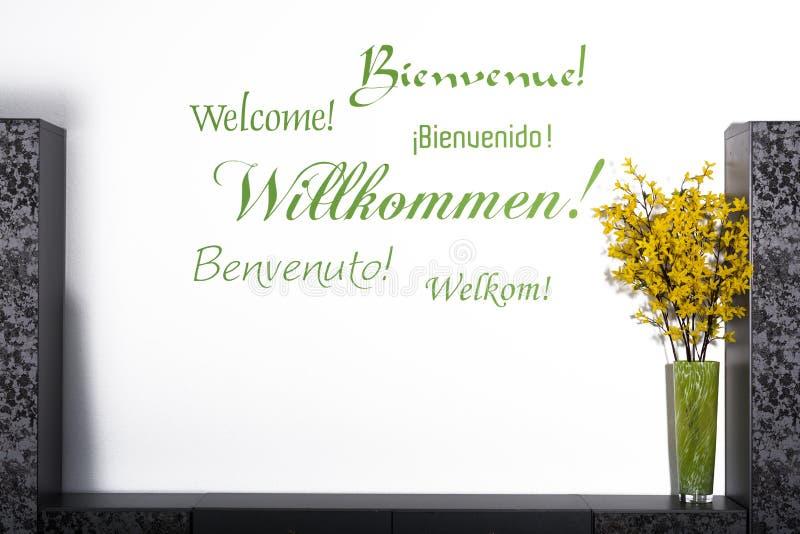 Lettrage bienvenu dans plusieurs langues sur un mur image stock