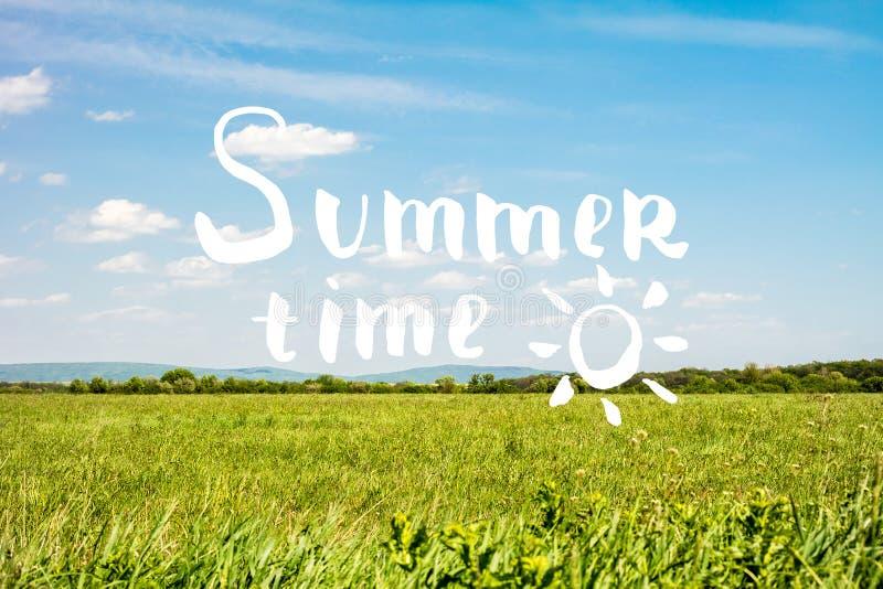 Lettrage d'heure d'été avec le fond de ciel et d'herbe images stock