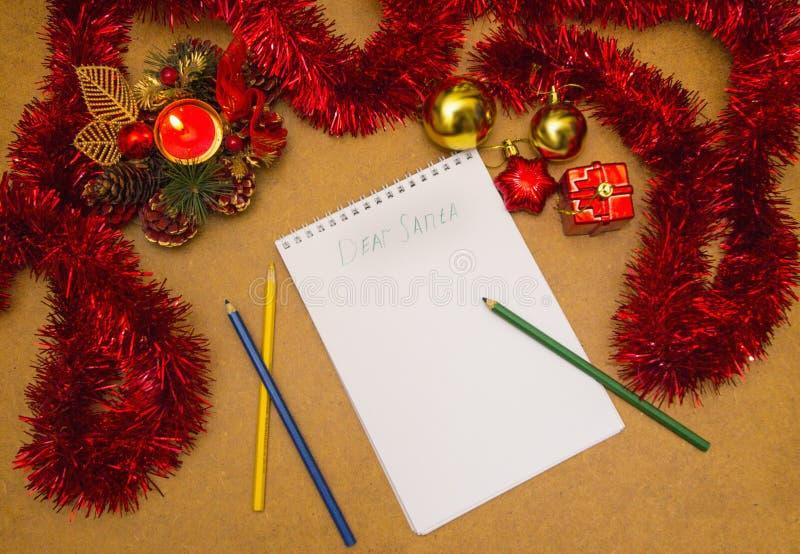 Lettre à Santa Claus avec une bougie, une tresse et des jouets de Noël images stock