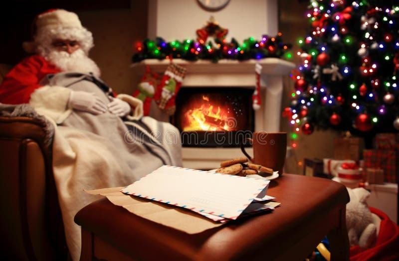 Lettre à Santa Claus près du cadeau et des bougies photographie stock libre de droits