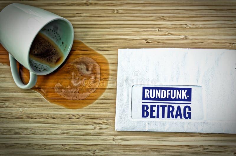 Lettre avec en l'allemand Rundfunkbeitrag dans le courrier par radio anglais et une tasse de café vidée d'effroi images libres de droits