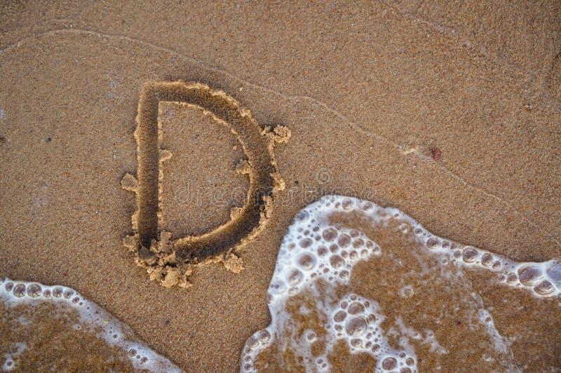 Lettre D d'alphabet manuscrite en plage de sable près de l'eau du Se images libres de droits