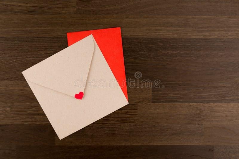 Lettre d'amour d'enveloppe Tow Envelopes Red et Brown avec un coeur sur le modèle en bois image libre de droits