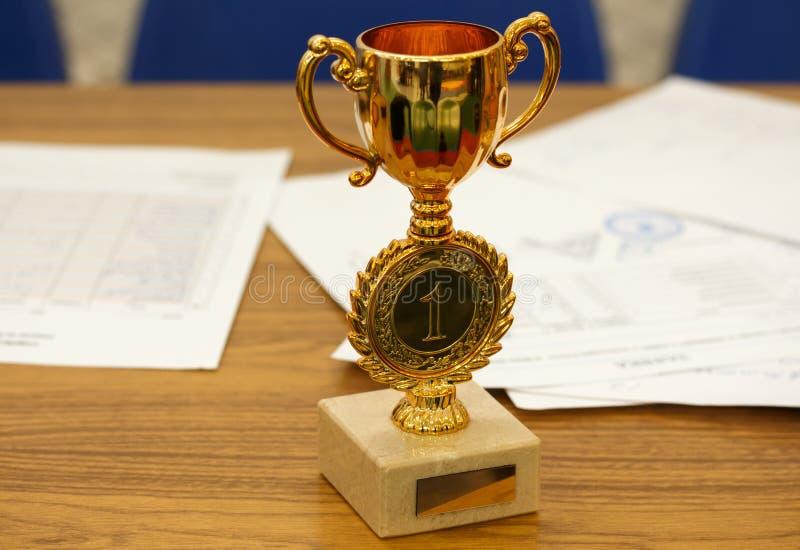 Lettre de félicitations Trophée et document de récompense de tasse d'or avec un joint sur la table en bois images libres de droits