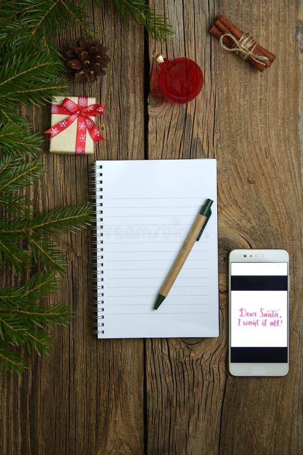 Lettre de Noël sur le fond en bois avec le téléphone portable, cadeaux, branches de sapin, décorations rouges photos libres de droits