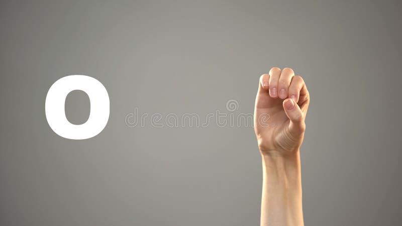 Lettre O dans la langue des signes, main sur le fond, communication pour sourd, le?on photos libres de droits