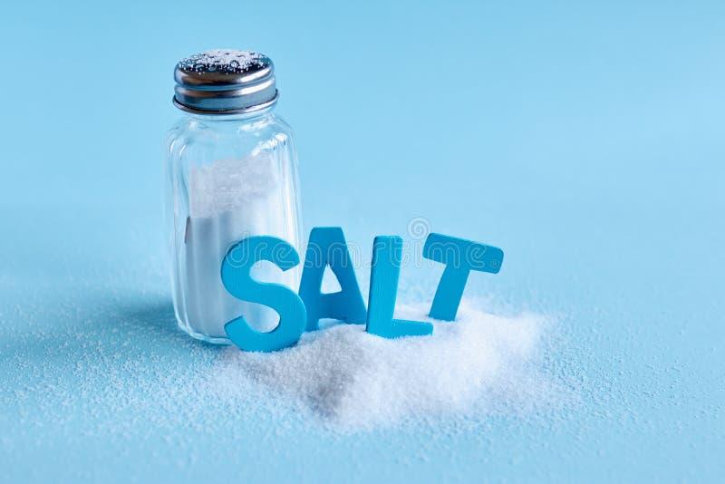 Lettres bleues orthographiant le sel de mot et le dispositif trembleur de sel image stock
