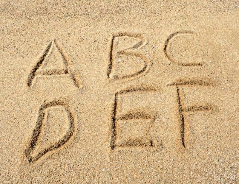 Lettres d'alphabet en sable sur la plage images stock