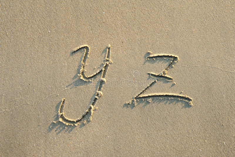 Lettres d'alphabet en sable sur la plage image stock