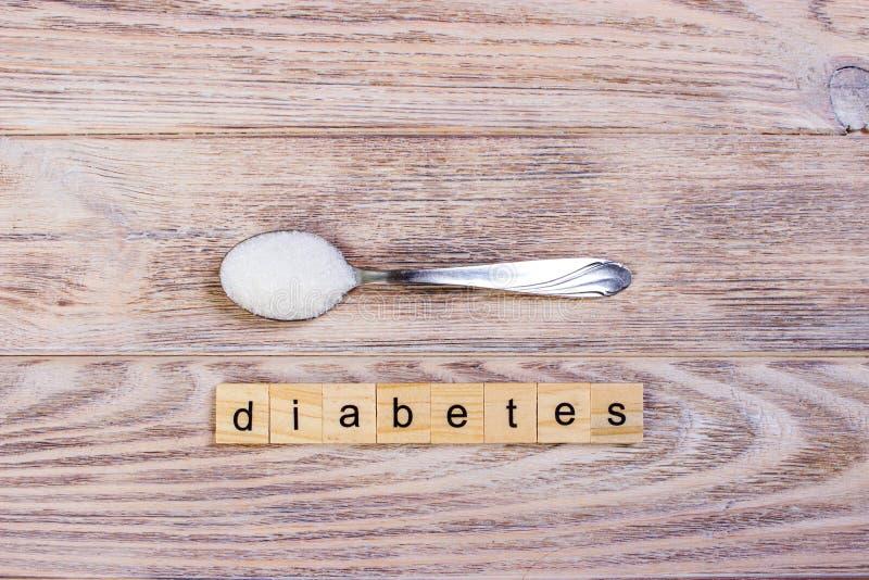 Lettres de bloc de diabète et pile en bois de sucre sur une cuillère photos libres de droits