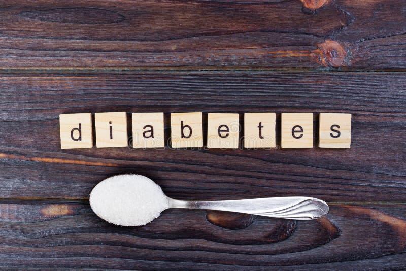 Lettres de bloc de diabète et pile en bois de sucre sur une cuillère images libres de droits