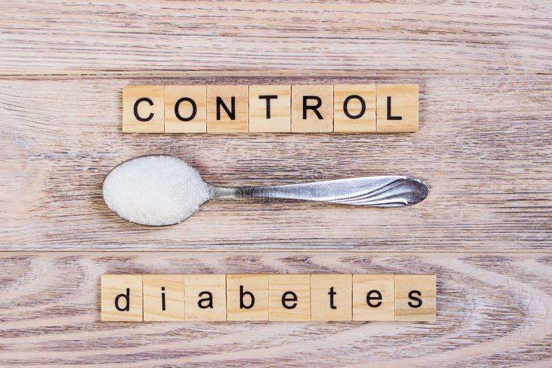 Lettres de bloc de gestion de diabète et pile en bois de sucre sur une cuillère photos stock