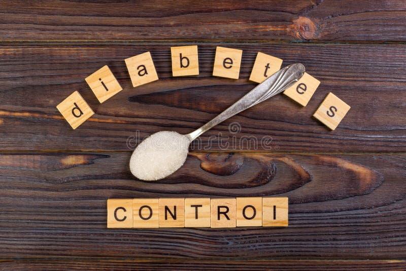 Lettres de bloc de gestion de diabète et pile en bois de sucre sur une cuillère photo stock