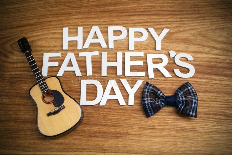Lettres de jour heureuses de pères avec la guitare sur le fond en bois Vue supérieure photographie stock