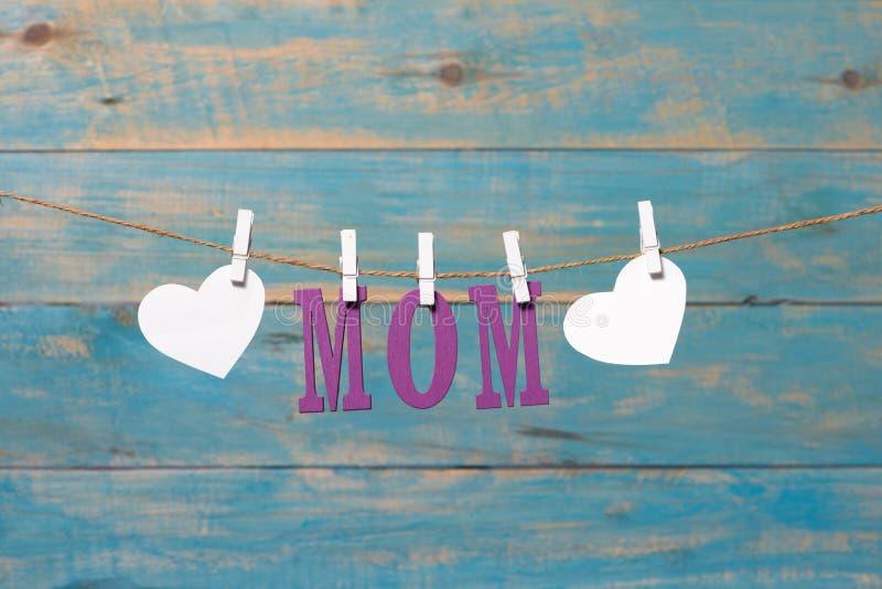 Lettres de MAMAN Message de jour de mères avec des coeurs accrochant avec des pinces à linge au-dessus du conseil en bois bleu photo stock